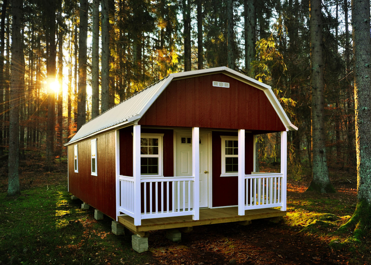 Red cabin with white trim in a wooded area