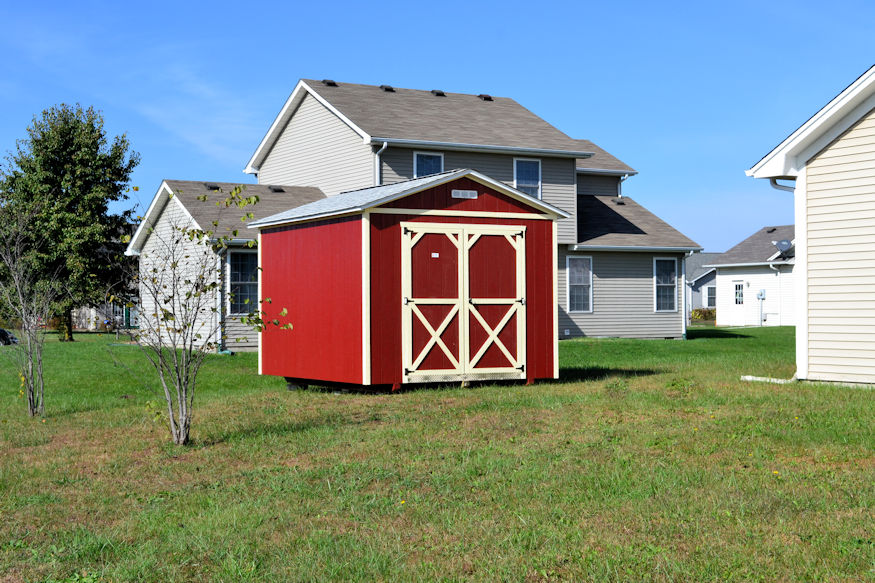 Red painted utility shed placed in the backyard of a small residential household next to several saplings