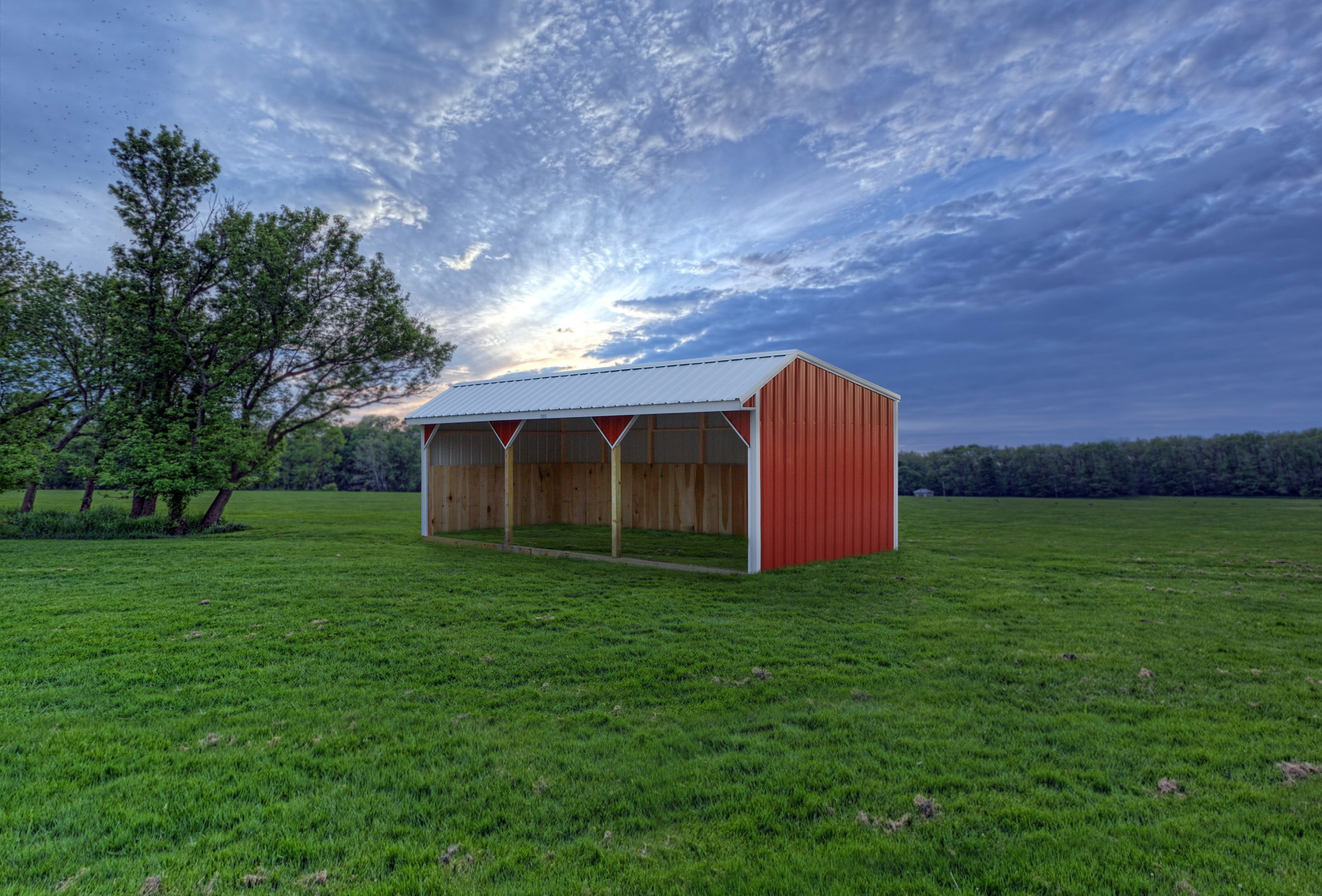 Red horse barn in an open pasture against a blue sky with clouds