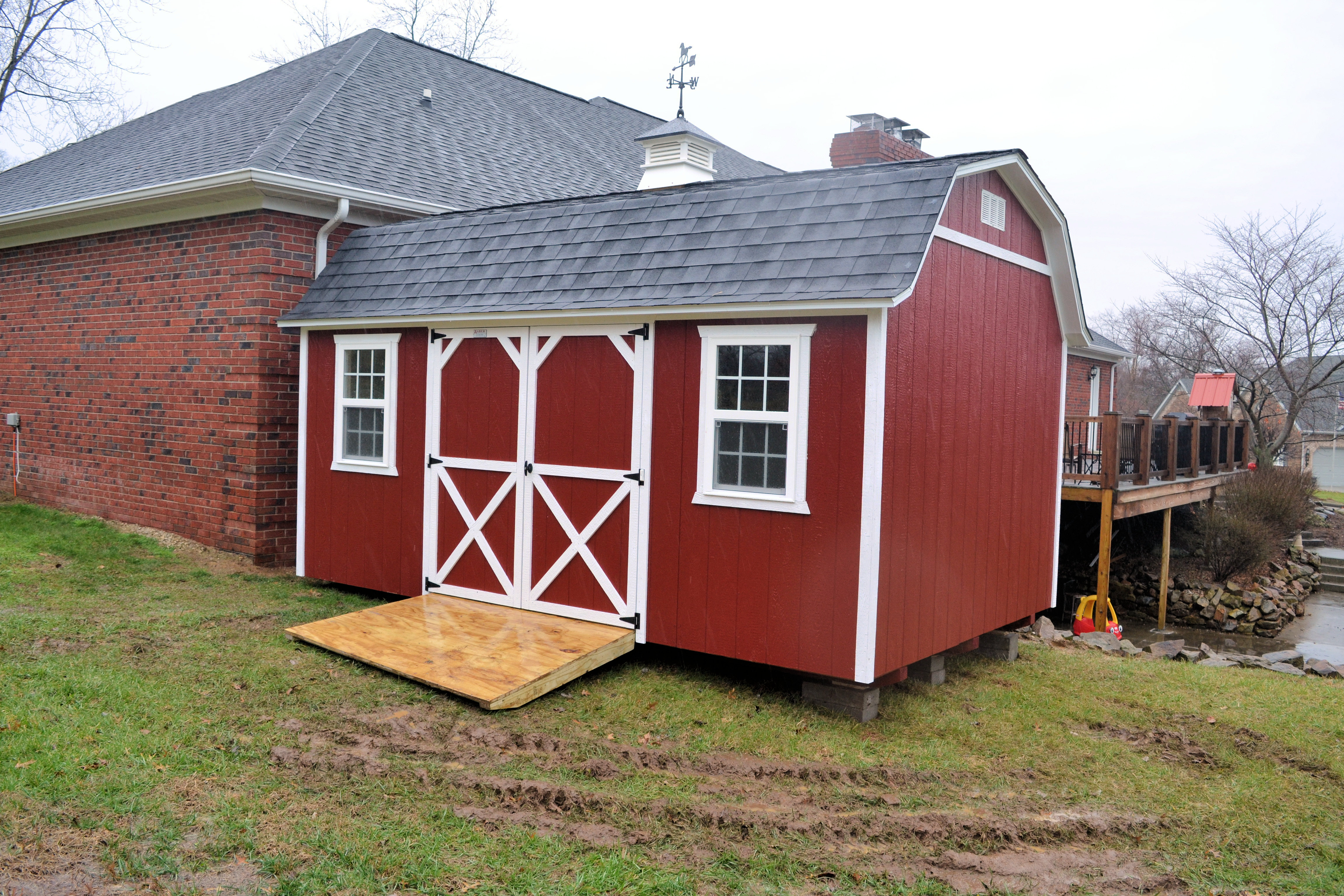 Red painted lofted garden shed is shown with optional treated ramp white detailing and double window and front door options