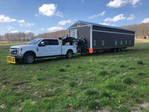 White pickup truck hauling a large shed