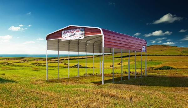 Steel carport with red roof in a grass field