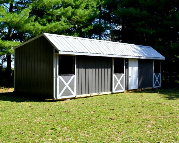 Gray and white deluxe horse barn in the grass with trees