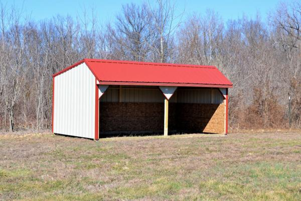 Red and white open horse barn in an empty field