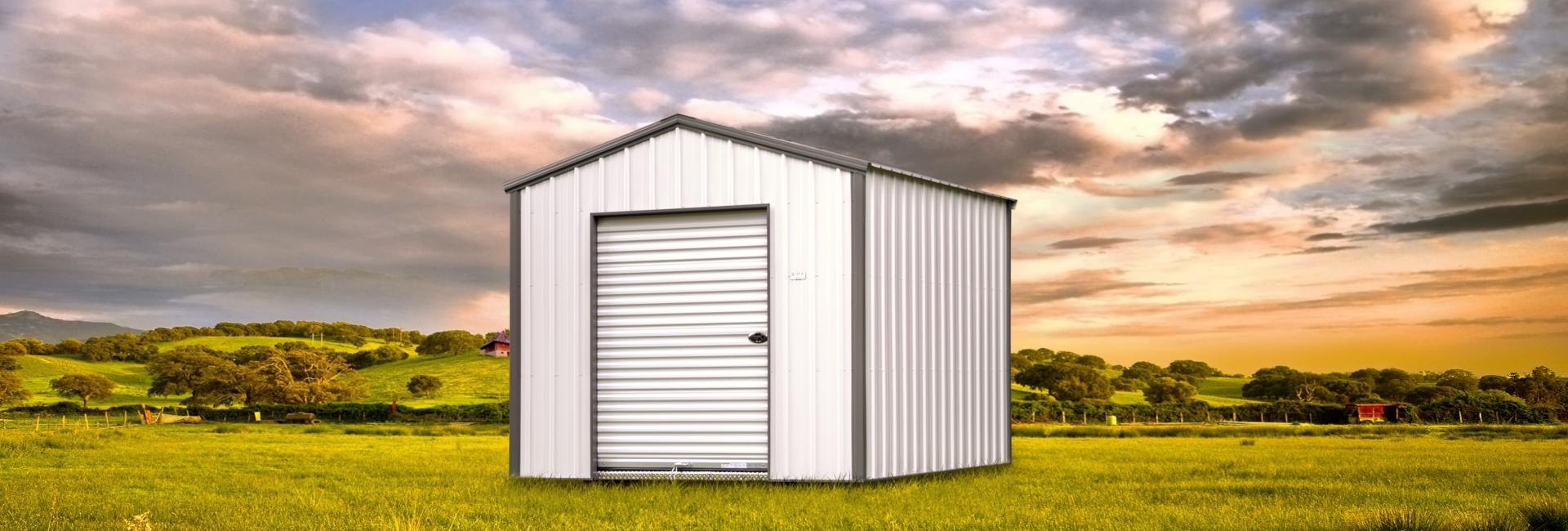 Portable economy storage shed featured in white with gray trim detail located in a green pasture at sunset