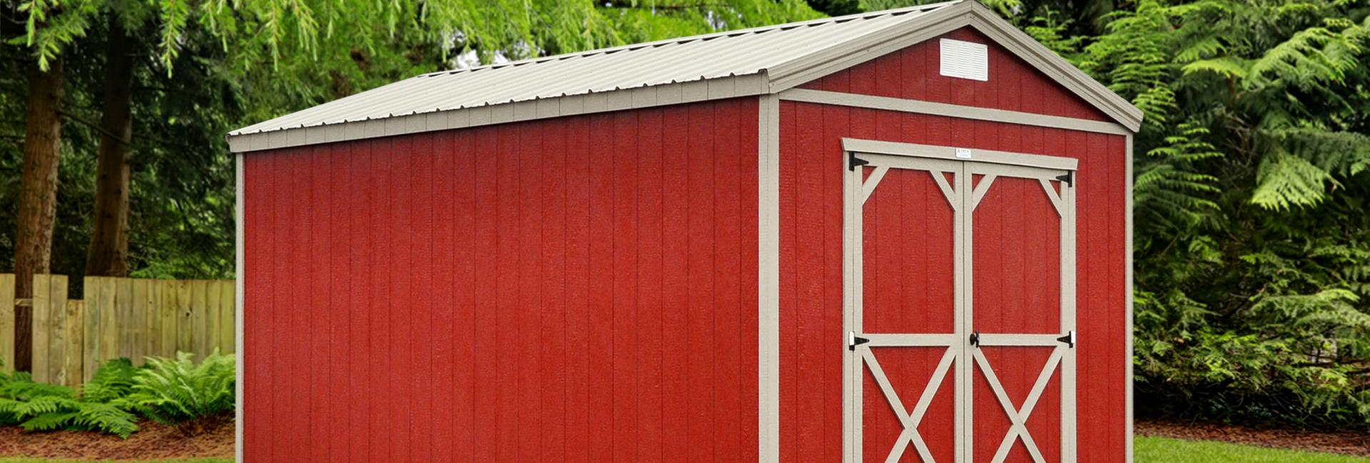 Painted utility shed in red with white trim detail placed in fenced in residential backyard next to various trees