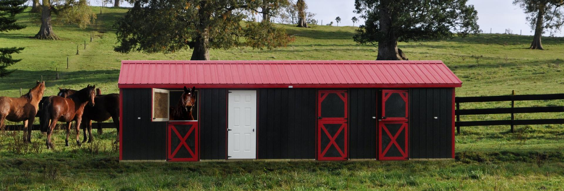Black and red horse barn with horses