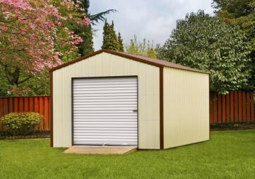 Tan metal storage building with a rolling door positioned in a pristine backyard with a cherry blossom tree