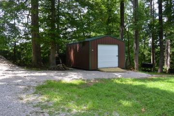 A portable metal storage shed with brown and evergreen trim located in residential backyard