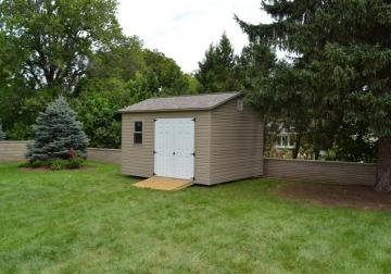 Residential fenced in backyard with portable garden shed in brown with white double front door and optional mower ramp