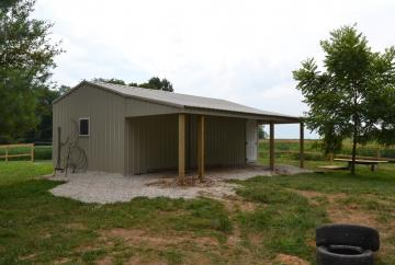 Tan portable barn with built in lean to located in a residential fenced backyard next to a pasture