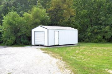 Gravel driveway leads down to a portable 12 by 20 metal storage building positioned under dense tree cover