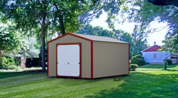 A red-trimmed portable storage barn with white doors located on a well manicured lawn on a sunny day