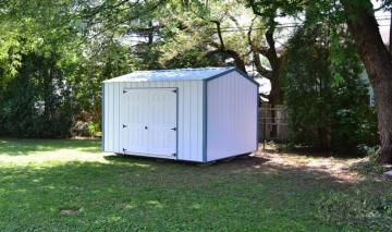 A grassy residential backyard houses a portable storage building with a double door option