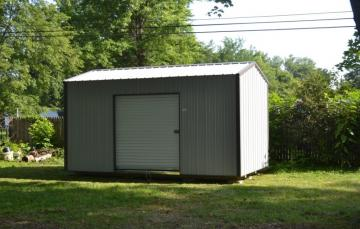 Raber's metal storage barn with a six foot rolling door option is positioned in a shaded backyard