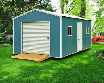 A custom-built blue portable building with white trim and roll door features an entry door two windows and treated ramp