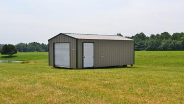 A portable metal storage shed with a seven foot wide rolling door and a full-sized entry door sits on a sloped grassy hill