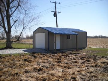 A rent to own portable metal shed with blue and white detailing positioned in a well maintained grassy backyard