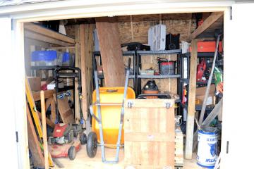 Internal perspective of a garden shed equipped with organizer packet for storing wheelbarrows skids tools and more