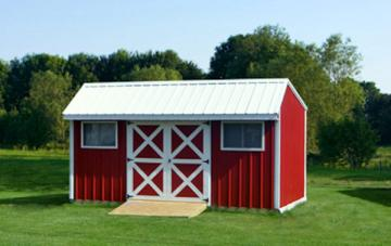 Red painted garden shed with white trim and dutch doors shown with optional tractor mower ramp in grassy valley