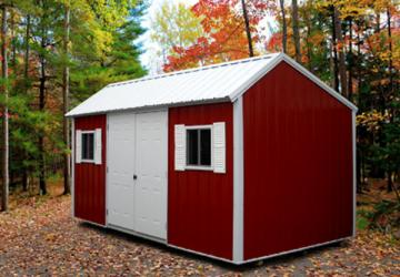 Red and white detailed garden shed with metal roof placed on hard surface surrounded by autumn foliage