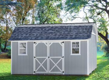 A gray garden shed with LP Smart siding and white trim detail placed under tree cover in residential backyard