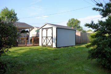 Utility shed placed in rear of small residential yard painted in tan with brown trim detail and double front doors