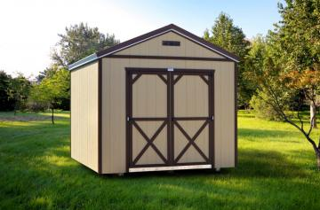 Tan and dark painted utility shed situated in a large open grassy area in between various trees and greenery
