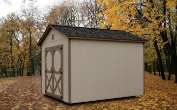 Autumn foliage and trees surround a painted utility shed colored in  tan with brown trim and front door detail