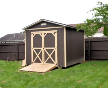 Dark brown painted utility shed with optional tractor ramp placed in rear of fenced in residential backyard