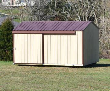 Portable storage building with metal siding and sliding door in a residential setting