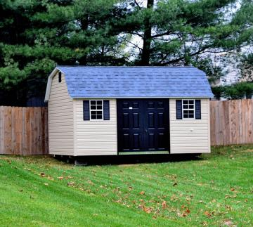 Vinyl sided lofted garden shed with shingle roof placed in grassy backyard next to wooden fence and pine trees