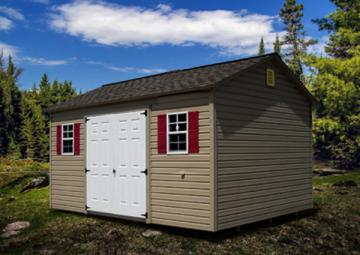 Tan 12 by 16 vinyl garden shed with red detailed shutters placed on mixed terrain under blue sky and clouds