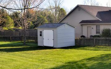 Vinyl garden shed is shown in grey with white double doors placed up against a picket wooden fence in residential backyard