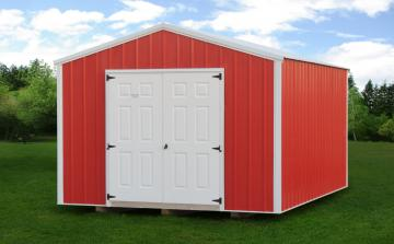Red metal portable building with white trim and double door positioned on top of grass under blue sky and white clouds