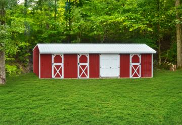Red deluxe horse barn with white trim in a grassy area