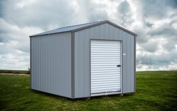 Gray on gray detailed portable storage shed located on mowed grassy backyard under a cloudy white sky