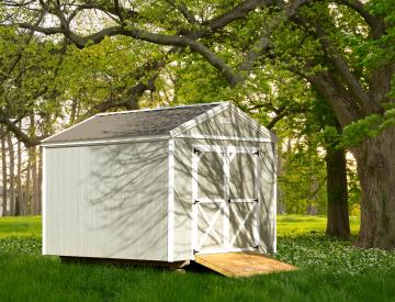 A small painted utility shed with white trim and front door detailing and optional mower ramp placed under a large tree