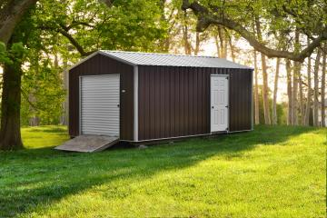 A metal storage building with brown paint white details and ramp access sits in a grassy shaded wooded area