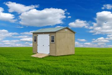 Garden shed in tan with white double front doors and tractor ramp positioned in a grassy plain under blue skies and clouds