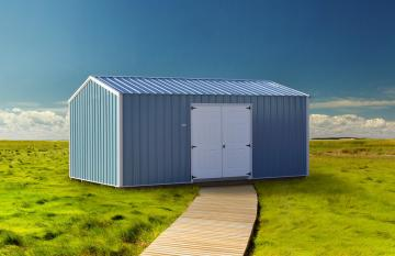 Blue and white portable metal shed with wooden plank walkway is placed on a grassy green valley under a clear blue sky