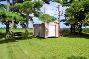 Tan storage shed with red trim and white roll door in the backyard of a residential neighborhood with several trees