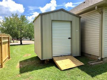 Tan economy storage shed with white roll door and optional treated ramp accessory placed in a residential backyard