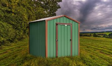 Small green storage shed with dark brown trim detailing and front door entry on a mowed lawn under dark cloudy sky