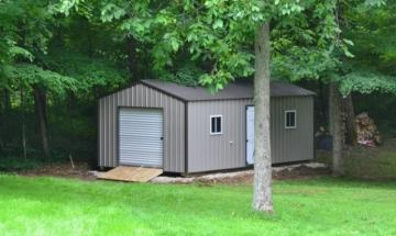 One large portable metal storage shed with tan and brown detailing and white entry door placed in wooded backyard
