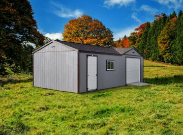 Gray garage combo shed in a field with autumn foliage