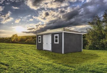 Gray four-way roof shed in a grassy area at dusk